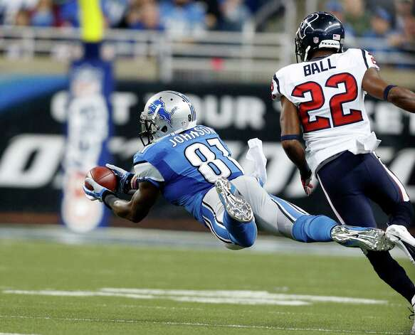 Detroit Lions wide receiver Calvin Johnson (81) makes a diving catch as Houston Texans defensive back Alan Ball (22) defends during the first quarter of an NFL football game at Ford Field in Detroit, Thursday, Nov. 22, 2012. (AP Photo/Rick Osentoski) Photo: Rick Osentoski, Associated Press / FR170444 AP