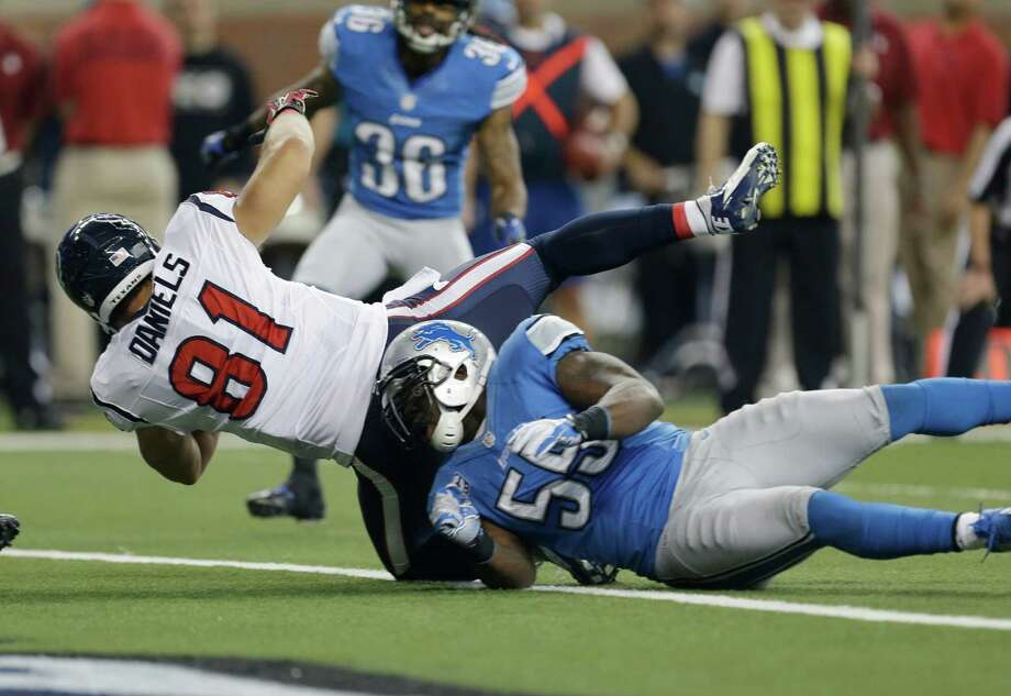 Houston Texans tight end Owen Daniels (81) falls over Detroit Lions middle linebacker Stephen Tulloch (55) into the end zone for a touchdown during the second quarter of an NFL football game at Ford Field in Detroit, Thursday, Nov. 22, 2012. (AP Photo/Paul Sancya) Photo: Paul Sancya, Associated Press / AP