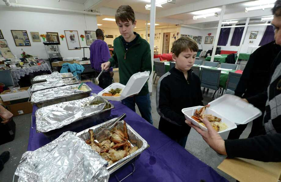 Volunteers Ryan and Rhys Williams of Clifton Park prepare take-out containers of turkey dinners to be delivered to various locations in Troy from the kitchen of The Missing Link AME Zion Church in Troy, N.Y. Nov 22, 2012.     (Skip Dickstein/Times Union) Photo: Skip Dickstein / 00020182A