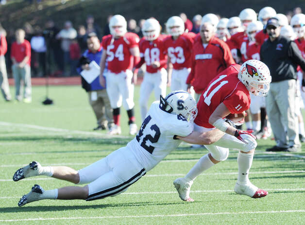 At left, Kevin Kearney # 42 of Staples tackles Alex McMurray # 11 of Greenwich during a running play by Greenwich in the FCIAC championship football game between Staples High School and Greenwich High School at Greenwich, Thursday afternoon, Nov. 22, 2012. Staples defeated Greenwich 48-30 to win the championship. Photo: Bob Luckey / Greenwich Time