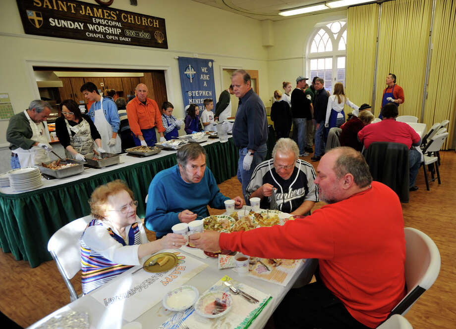 Seated from left, Esther Forlini, Michael Critelli, Arthur Wetmore and Brett Bolmer enjoy a Thanksgiving meal at Saint James Episcopal Church in Danbury on Thursday, Nov. 22, 2012. Photo: Jason Rearick / The News-Times