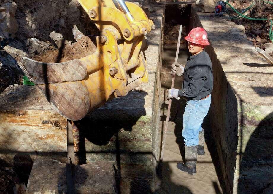 Arturo Ramirez works in the 20-foot-long stone sluiceway in Brackenridge Park Photo: William Luther, San Antonio Express-News / © 2012 San Antonio Express-News