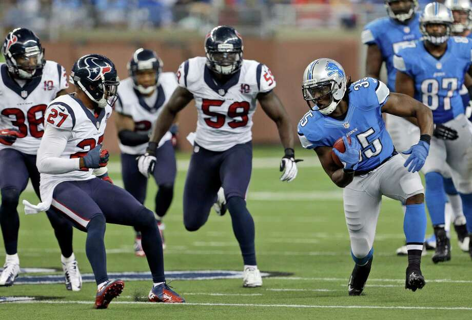 Detroit Lions running back Joique Bell (35) runs around the defense of Houston Texans defensive back Quintin Demps (27), free safety Danieal Manning (38) and linebacker Whitney Mercilus (59) during the fourth quarter of an NFL football game at Ford Field in Detroit, Thursday, Nov. 22, 2012. (AP Photo/Paul Sancya) Photo: Paul Sancya, Associated Press / AP