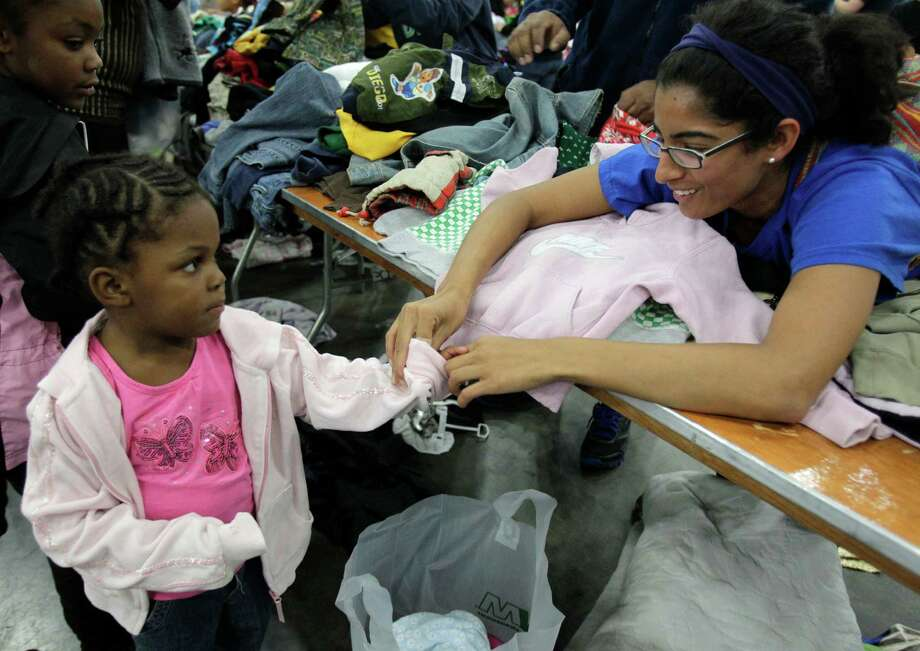 Volunteer Julie Mathew helps roll up the sleeves for Khoe Blanton, 3, after giving her a jacket during the Big Super Feast at the George R. Brown Convention Center Thursday, Nov. 22, 2012, in Houston. Photo: Melissa Phillip, Houston Chronicle / © 2012 Houston Chronicle