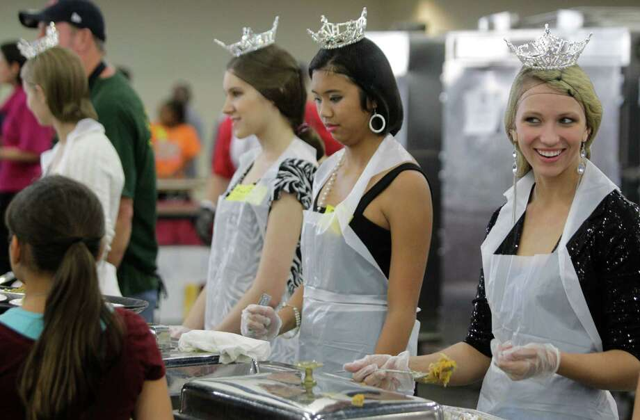 Kate Samuelson, left, Tiffany Dimaano, center, and Niki Noblett all volunteers from the Miss America organization serve food to people during the Big Super Feast at the George R. Brown Convention Center Thursday, Nov. 22, 2012, in Houston. Photo: Melissa Phillip, Houston Chronicle / © 2012 Houston Chronicle