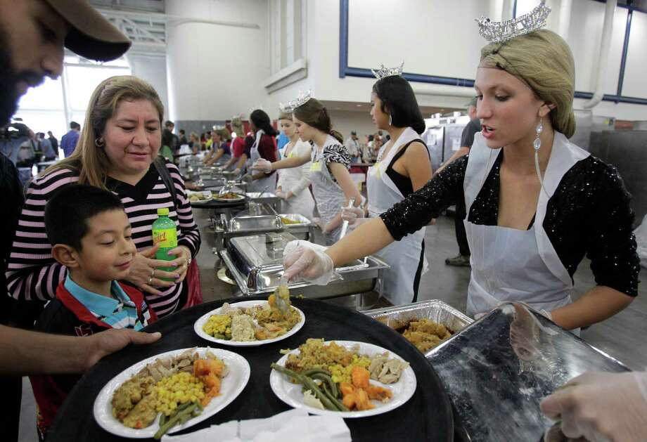 Niki Noblett a volunteer from the Miss America organization serves food to Omar Cambron, 7, and his mother, Juana Cambron during the Big Super Feast at the George R. Brown Convention Center Thursday, Nov. 22, 2012, in Houston. Photo: Melissa Phillip, Houston Chronicle / © 2012 Houston Chronicle