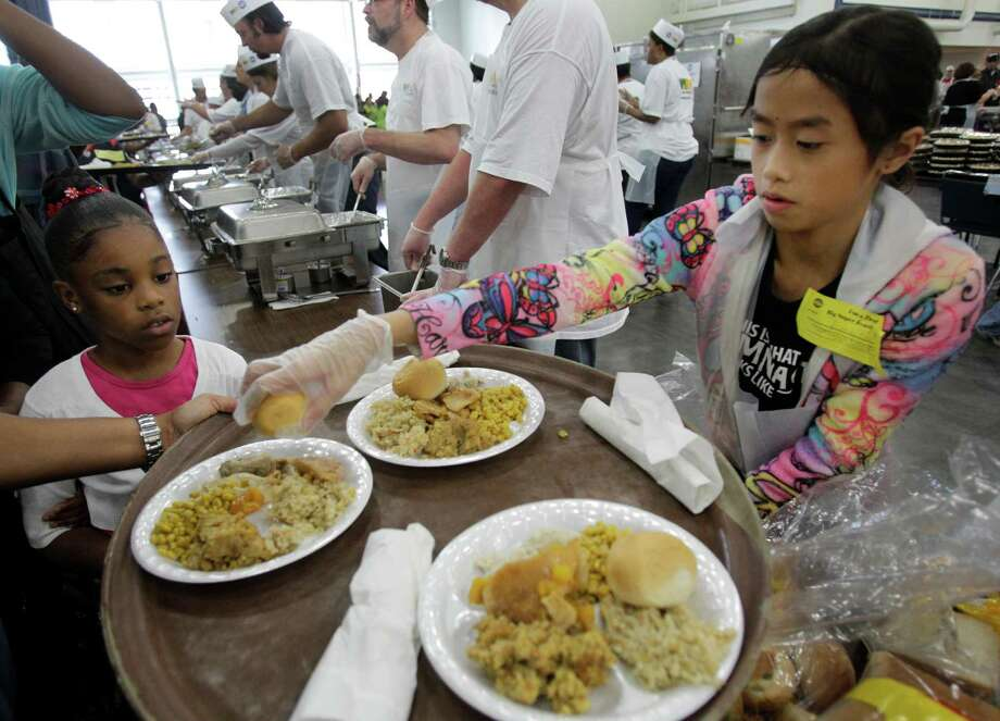 Demi Breaur, 7, left, watch as volunteer Emily Routbort, 11, serves food to during the Big Super Feast at the George R. Brown Convention Center Thursday, Nov. 22, 2012, in Houston. Photo: Melissa Phillip, Houston Chronicle / © 2012 Houston Chronicle