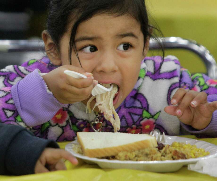 Luna Tobar, 3, tackles her food during the Big Super Feast at the George R. Brown Convention Center Thursday, Nov. 22, 2012, in Houston. Photo: Melissa Phillip, Houston Chronicle / © 2012 Houston Chronicle
