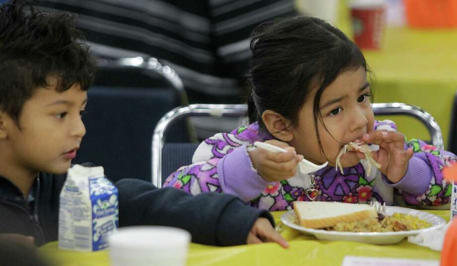 Israel Delgadillo, 3, left, and Luna Tobar, 3, eat during the Big Super Feast at the George R. Brown Convention Center Thursday, Nov. 22, 2012, in Houston. Photo: Melissa Phillip, Houston Chronicle / © 2012 Houston Chronicle