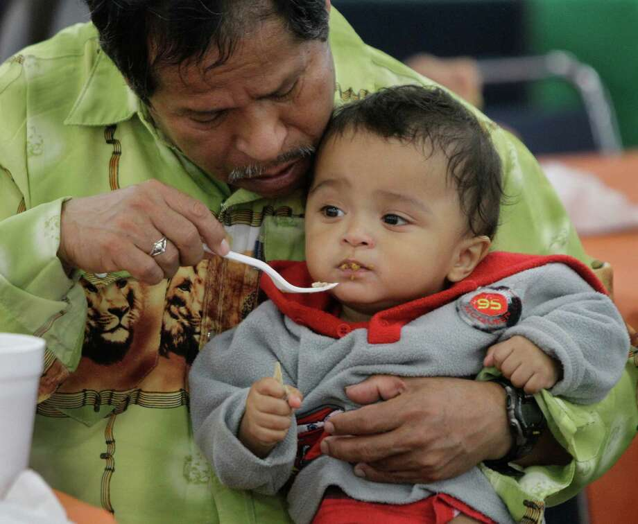 Miguel Albot feeds his grandson, Ango, 2, during the Big Super Feast at the George R. Brown Convention Center Thursday, Nov. 22, 2012, in Houston. Photo: Melissa Phillip, Houston Chronicle / © 2012 Houston Chronicle
