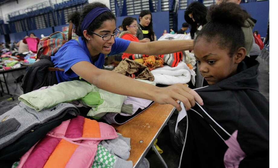 Volunteer Julie Mathew helps Courtney Blanton, 9, try on a jacket during the Big Super Feast at the George R. Brown Convention Center Thursday, Nov. 22, 2012, in Houston. Photo: Melissa Phillip, Houston Chronicle / © 2012 Houston Chronicle
