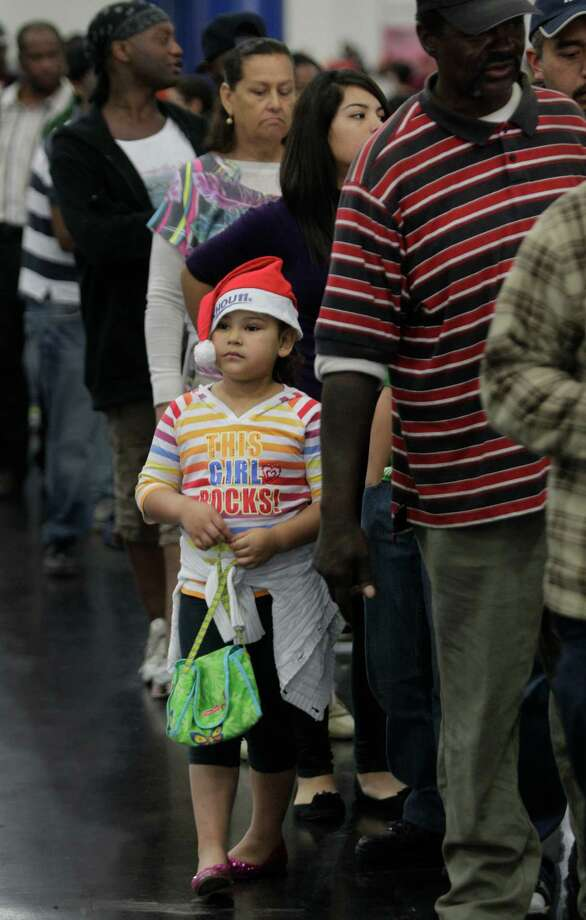 Linda Segura, 6, waits in line during the Big Super Feast at the George R. Brown Convention Center Thursday, Nov. 22, 2012, in Houston. Photo: Melissa Phillip, Houston Chronicle / © 2012 Houston Chronicle