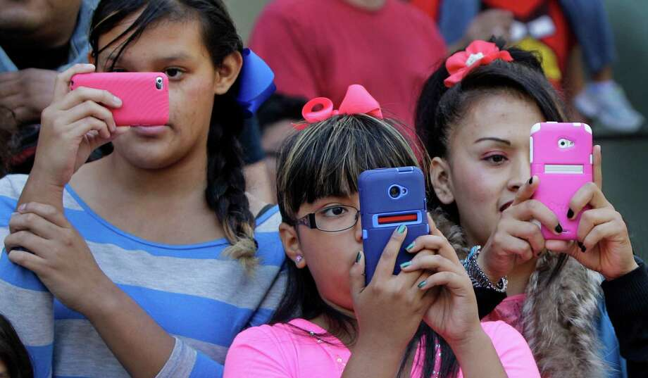 Jennifer Garcia, 13, left, her cousin, Paola Diaz, 10, and  her sister, Silvia Barrera, right, capture the action on their cell phones during the 63rd Annual Houston Holiday Parade in downtown Thursday, Nov. 22, 2012, in Houston. Photo: Melissa Phillip, Houston Chronicle / © 2012 Houston Chronicle