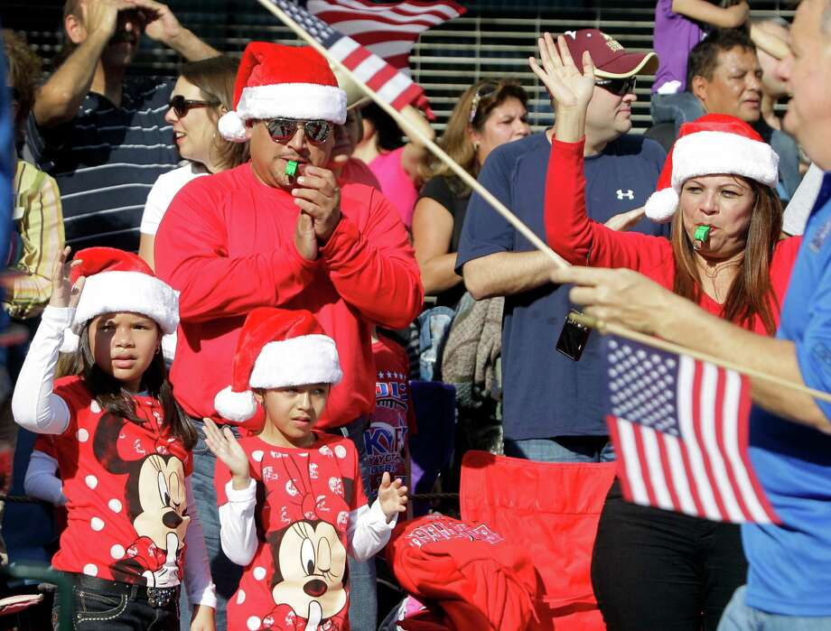 Juan Sandoval with his wife, Nelly Sandoval, and their children Amy, 11, left, and Andrea, 7, right, all in Santa hats enjoy the 63rd Annual Houston Holiday Parade in downtown Thursday, Nov. 22, 2012, in Houston. Photo: Melissa Phillip, Houston Chronicle / © 2012 Houston Chronicle