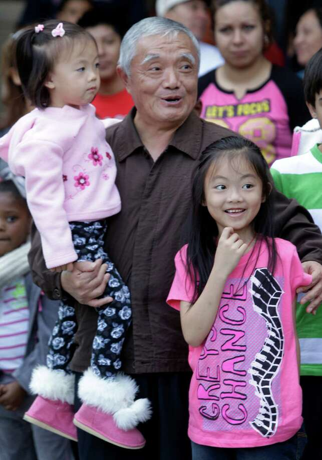 Ruilin Luo with his grandchildren, Jenna Li, 3, and Tina Li, 7, right,  enjoy the 63rd Annual Houston Holiday Parade in downtown Thursday, Nov. 22, 2012, in Houston. Photo: Melissa Phillip, Houston Chronicle / © 2012 Houston Chronicle