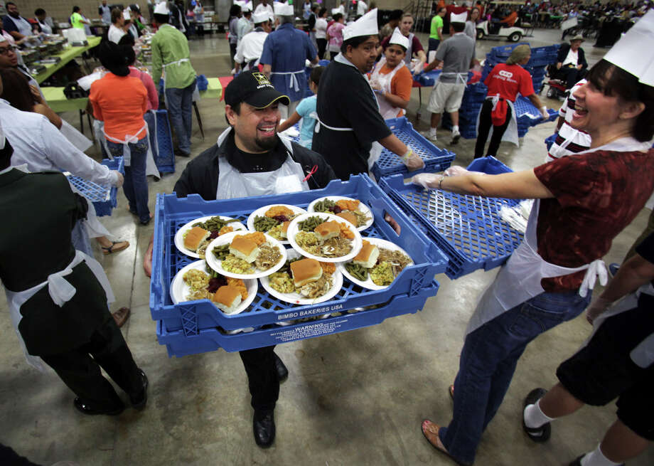 A cheerful Elvis Hernandez (center) carries two trays full of turkey dinners for those attending the Raul Jimenez Thanksgiving Dinner, which served 24,800 meals during the 33rd annual feast. Photo: Bob Owen, San Antonio Express-News / © 2012 San Antonio Express-News