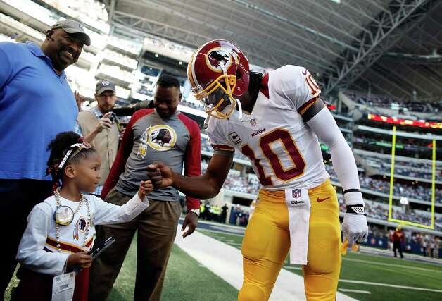 Robert Griffin III #10 of the Washington Redskins greets a young fan before taking on the Dallas Cowboys on Thanksgiving Day at Cowboys Stadium on November 22, 2012 in Arlington, Texas. Photo: Tom Pennington, Getty Images / 2012 Getty Images