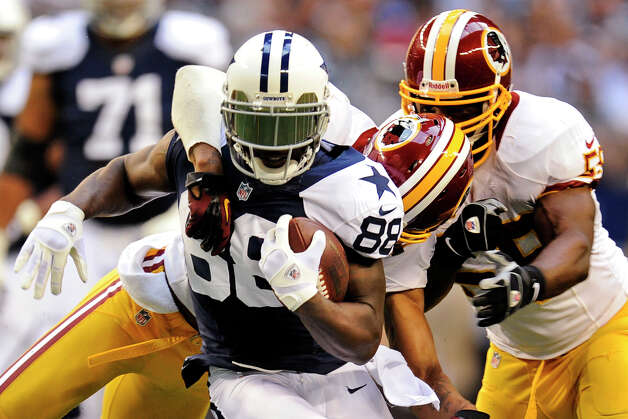 Dallas Cowboys wide receiver Dez Bryant (88) tries to break a tackle by Washington Redskins' Cedric Griffin, rear, and London Fletcher, right, after a reception in the first half of an NFL football game, Thursday, Nov. 22, 2012, in Arlington, Texas. (AP Photo/Matt Strasen) Photo: Matt Strasen, Associated Press / FR170476 AP