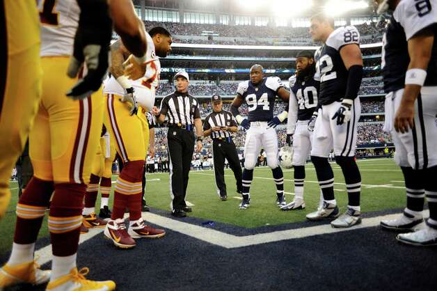 Refere Bill Leavy, center left, talks to the Washington Redskins captains after they won the toss in a NFL football game against the Dallas Cowboys Thursday, Nov. 22, 2012 in Arlington, Texas. (AP Photo/Matt Strasen) Photo: Matt Strasen, Associated Press / FR170476 AP