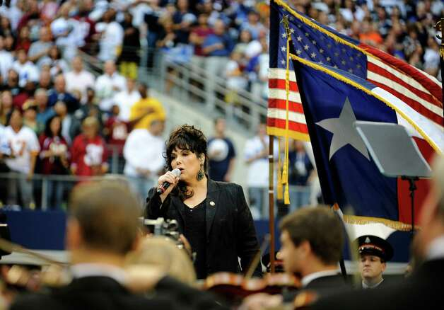 Ann Wilson of the group Heart sings the national anthem accompanied by members of the Dallas Symphony Orchestra before an NFL football game between the Washington Redskins and Dallas Cowboys Thursday, Nov. 22, 2012, in Arlington, Texas. (AP Photo/Matt Strasen) Photo: Matt Strasen, Associated Press / FR170476 AP