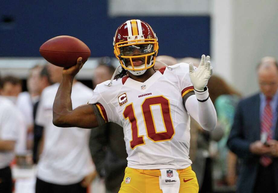 Washington Redskins quarterback Robert Griffin III (10) passes as he warms up before an NFL football game against the Dallas Cowboys Thursday, Nov. 22, 2012, in Arlington, Texas. (AP Photo/Tim Sharp) Photo: Tim Sharp, Associated Press / FR62992 AP