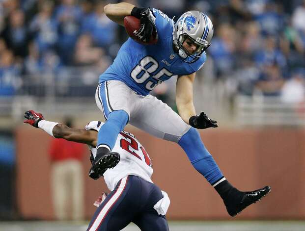 Tony Scheffler #85 of the Detroit Lions jumps over Brice McCain #21 of the Houston Texans after a overtime catch at Ford Field on November 22, 2012 in Detroit, Michigan. Houston won the game 34-31. Photo: Gregory Shamus, Getty Images / 2012 Getty Images