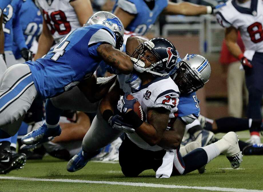Detroit Lions strong safety Erik Coleman (24) and linebacker Stephen Tulloch (55) stop Houston Texans running back Arian Foster (23) near the goal line in the second half of an NFL football game in Detroit, Thursday, Nov. 22, 2012. Houston won 34-31. (AP Photo/Paul Sancya) Photo: Paul Sancya, Associated Press / AP