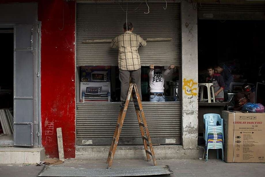 Palestinian men repair a shop damaged during the Israeli shelling of Gaza. The Hamas militant group celebrated after the cease-fire went into effect. Photo: Bernat Armangue, Associated Press