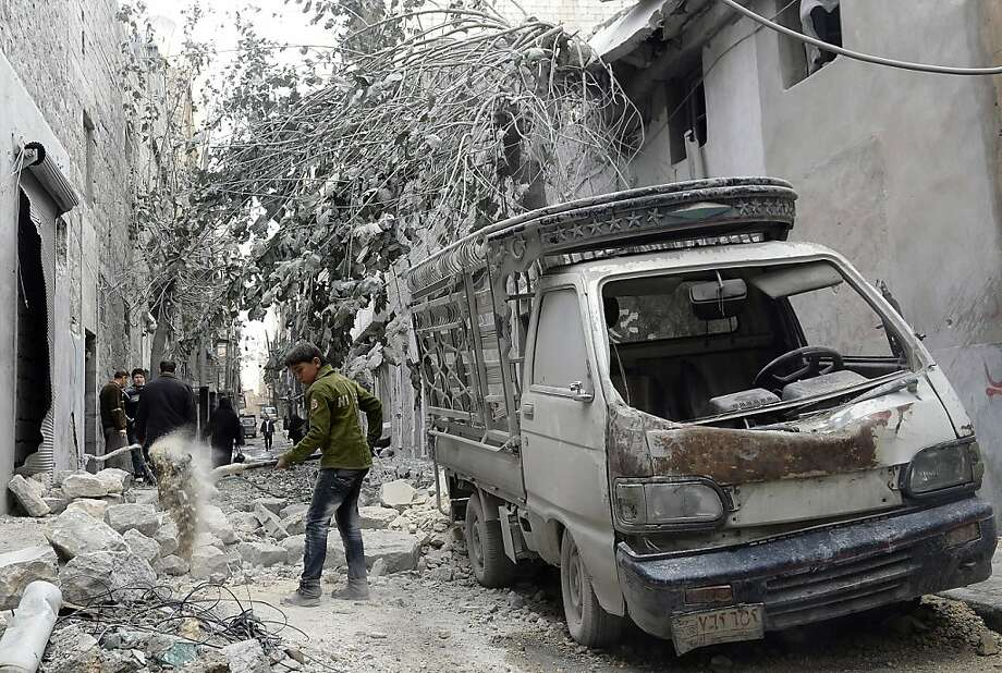 A boy cleans debris after Syrian forces damaged Aleppo's Dar al-Shifa hospital, killing 15 and impairing a remaining source of medical care. Photo: Francisco Leong, AFP/Getty Images