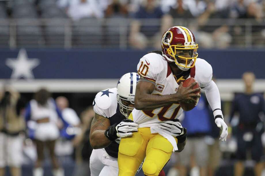 Robert Griffin III #10 of the Washington Redskins scrambles with the ball before being sacked by Jason Hatcher #97 of the Dallas Cowboys on Thanksgiving Day at Cowboys Stadium on November 22, 2012 in Arlington, Texas. Photo: Tom Pennington, Getty Images / 2012 Getty Images