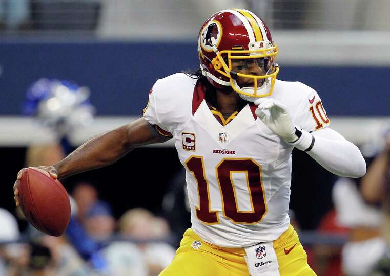 Robert Griffin III #10 of the Washington Redskins scrambles with the ball before being sacked by Jas