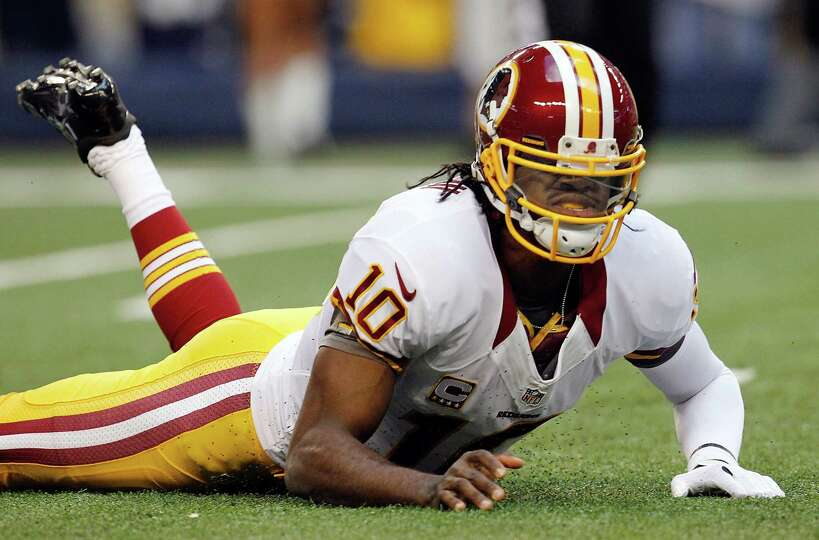 Robert Griffin III #10 of the Washington Redskins reacts after being sacked by Jason Hatcher #97 of
