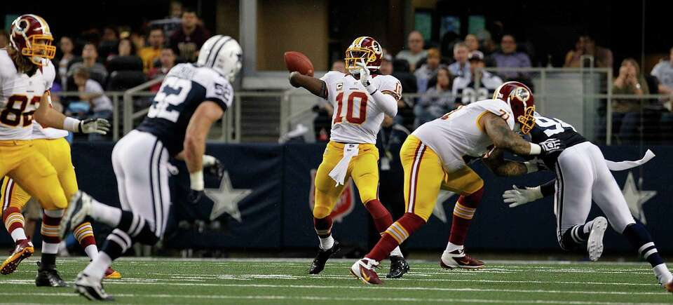 Robert Griffin III #10 of the Washington Redskins looks for an open receiver against the Dallas Cowb