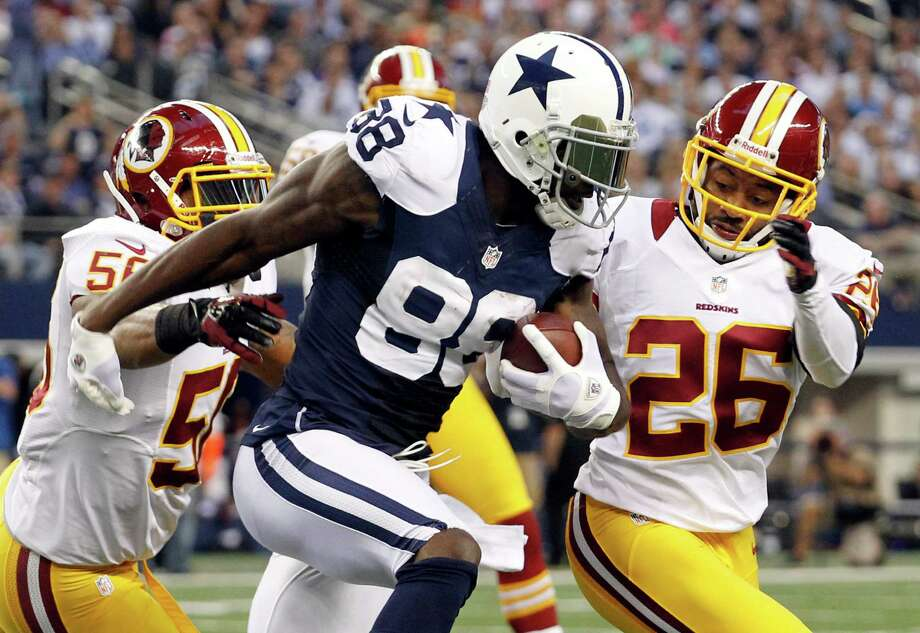 Dallas Cowboys wide receiver Dez Bryant (88) is tackled by Washington Redskins' Perry Riley (56) and Josh Wilson (26) ona short run in the first half of an NFL football game, Thursday, Nov. 22, 2012, in Arlington, Texas. (AP Photo/Tim Sharp) Photo: Tim Sharp, Associated Press / FR62992 AP
