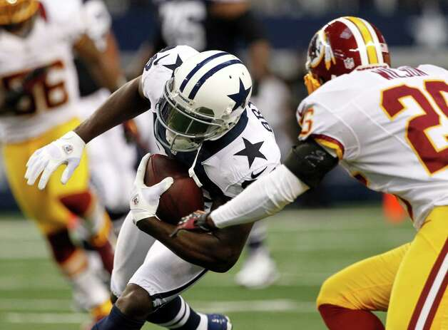 Dallas Cowboys wide receiver Dez Bryant (88) runs after a reception from Washington Redskins' Josh Wilson (26) before Bryant fumbled on the play in the first half of an NFL football game Thursday, Nov. 22, 2012 in Arlington, Texas. (AP Photo/Tim Sharp) Photo: Tim Sharp, Associated Press / FR62992 AP