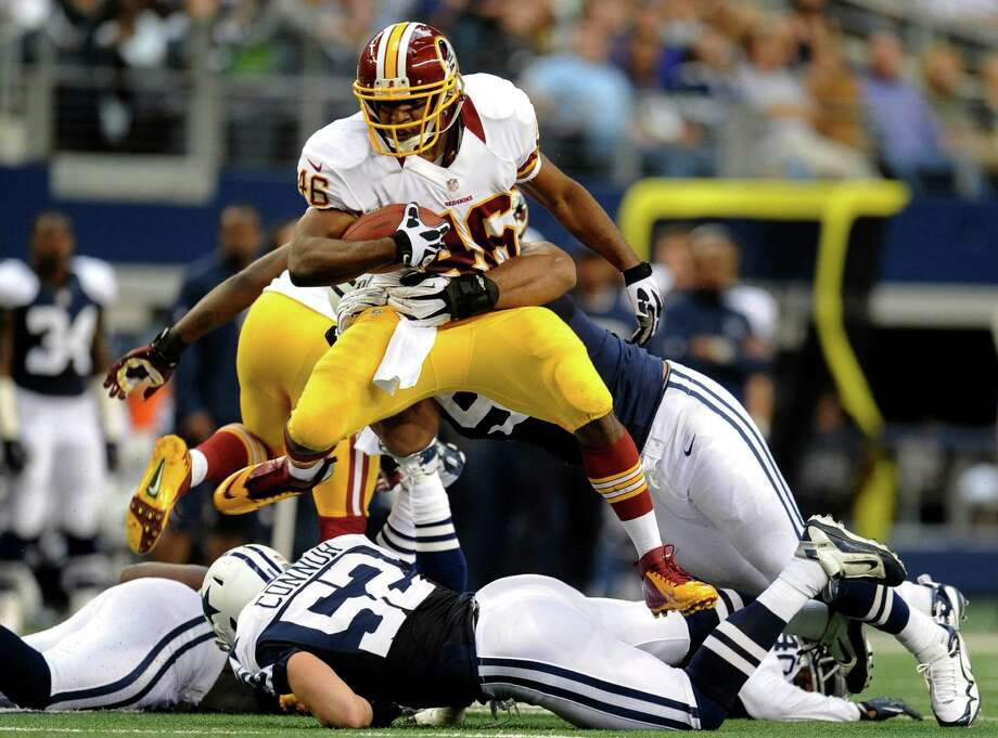 Washington Redskins running back Alfred Morris (46) leaps over Dallas Cowboys' Dan Connor (52) as he tries to escape a tackle by Jason Hatcher, rear, in the first half of an NFL football game, Thursday, Nov. 22, 2012, in Arlington, Texas. (AP Photo/Matt Strasen) Photo: Matt Strasen, Associated Press / FR170476 AP