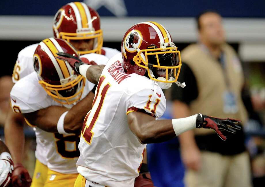 Washington Redskins' Aldrick Robinson (11) celebrates his touchdown catch with Pierre Garcon (88) and Darrel Young, rear, in the first half of an NFL football game against the Dallas Cowboys, Thursday, Nov. 22, 2012, in Arlington, Texas. (AP Photo/Matt Strasen) Photo: Matt Strasen, Associated Press / FR170476 AP