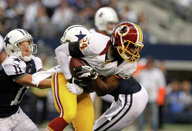 Washington Redskins strong safety DeJon Gomes (24) escapes tackles by Dallas Cowboys' Cole Beasley (11) and Dez Bryant, center rear, after recovering a fumble by Bryant in the first half of an NFL football game Thursday, Nov. 22, 2012 in Arlington, Texas. (AP Photo/Tim Sharp) Photo: Tim Sharp, Associated Press / FR62992 AP