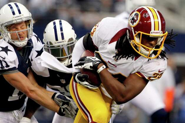 Washington Redskins strong safety DeJon Gomes (24) escapes tackles by Dallas Cowboys' Cole Beasley (11) and Dez Bryant, center, after recovering a fumble by Bryant in the first half of an NFL football game, Thursday, Nov. 22, 2012, in Arlington, Texas. (AP Photo/Tim Sharp) Photo: Tim Sharp, Associated Press / FR62992 AP