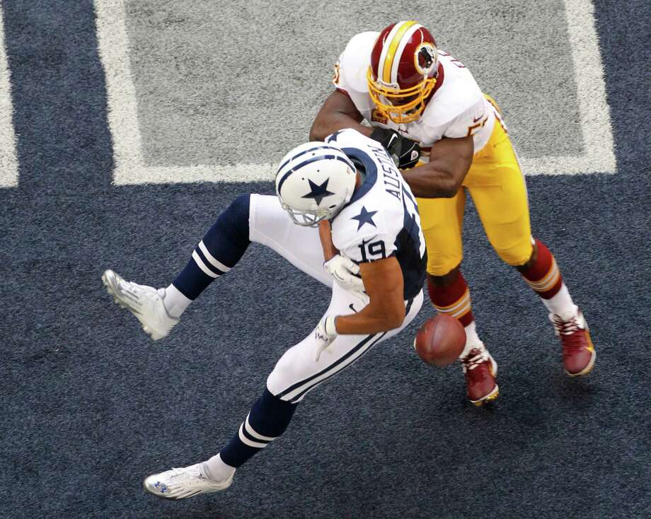 Dallas Cowboys wide receiver Miles Austin (19) is unable to come down with a pass in the end zone as Washington Redskins' London Fletcher (59) applies a hit in the first half of an NFL football game Thursday, Nov. 22, 2012, in Arlington, Texas. (AP Photo/Tim Sharp) Photo: Tim Sharp, Associated Press / FR62992 AP