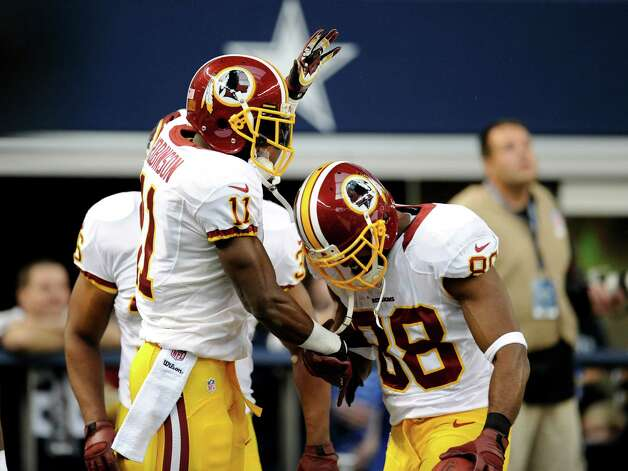 Washington Redskins' Aldrick Robinsonn celebrates his touchdown catch with Pierre Garcon (88) and Darrel Young, rear, in the first half of an NFL football game against the Dallas Cowboys Thursday, Nov. 22, 2012 in Arlington, Texas. (AP Photo/Matt Strasen) Photo: Matt Strasen, Associated Press / FR170476 AP