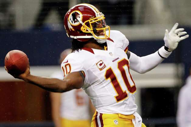 Washington Redskins quarterback Robert Griffin III (10) reaches back to throw a touchdown pass to Aldrick Robinson in the first half of an NFL football game against the Dallas Cowboys, Thursday, Nov. 22, 2012, in Arlington, Texas. (AP Photo/Tim Sharp) Photo: Tim Sharp, Associated Press / FR62992 AP