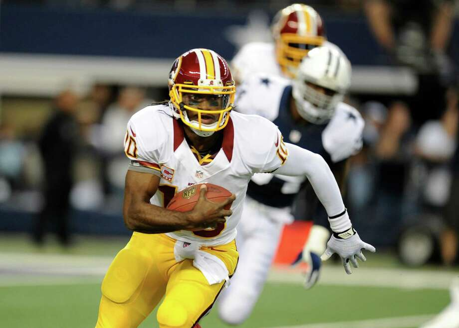 Washington Redskins quarterback Robert Griffin III (10) scrambles out of the pocket in the first half of an NFL football game against the Dallas Cowboys Thursday, Nov. 22, 2012, in Arlington, Texas. (AP Photo/Matt Strasen) Photo: Matt Strasen, Associated Press / FR170476 AP