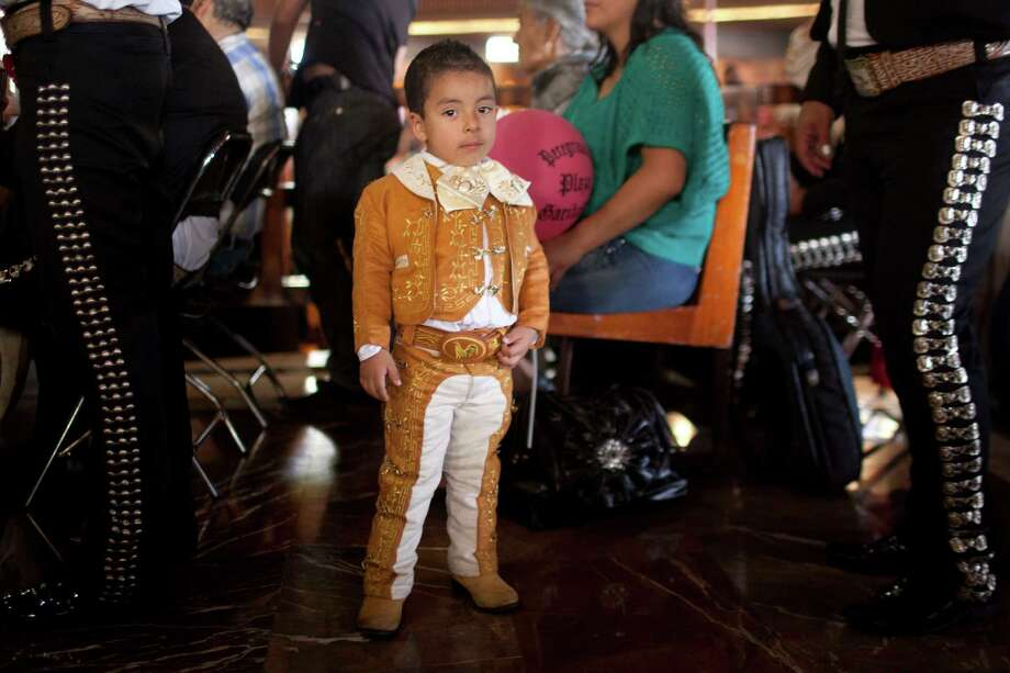 Cristopher Adair, 3, looks at the camera beside his father on the right, a Mariachi musician, during a mass in honor of Saint Cecilia, Mexico City, Thursday, Nov. 22, 2012.  Hundreds of people walked in procession to the Basilica of Guadalupe to honor Saint Cecilia, the patron saint of music. (AP Photo/Alexandre Meneghini) Photo: Alexandre Meneghini, Associated Press / AP