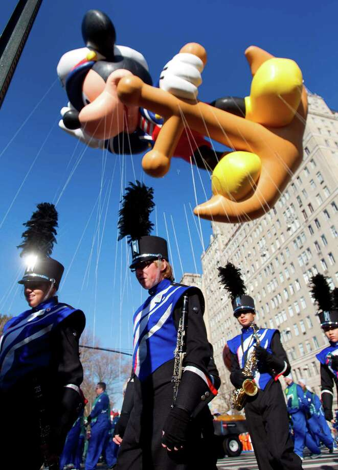 Members of the Oak Ridge High School Marching Band walk under a Mickey Mouse balloon as they make their way to the start of the Macy's Thanksgiving Day Parade Thursday, Nov. 22, 2012, in New York City. Photo: Brett Coomer, Houston Chronicle / © 2012 Houston Chronicle