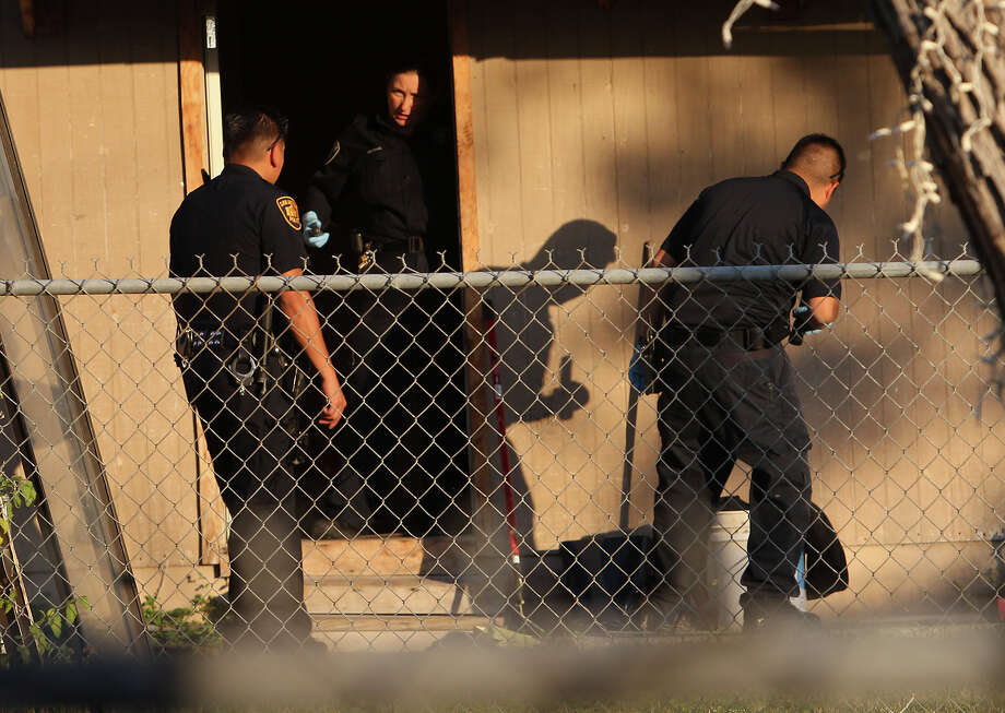Police investigate the scene where a man was shot and killed at a home in the 2000 block of Delgado Street. Police say they were not notified of the shooting for almost 12 hours. Photo: Kin Man Hui, San Antonio Express-News / © 2012 San Antonio Express-News