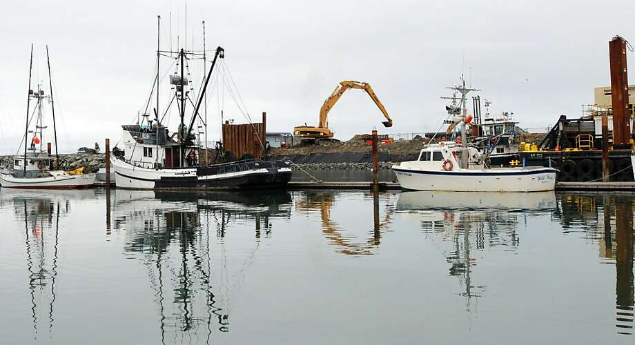 A large backhoe operates at the Crescent City boat basin, above, where work goes on to repair the damage done by the March 2011 tsunami, left, and build up the harbor to withstand any in the future. Photo: Jeff Barnard, Associated Press