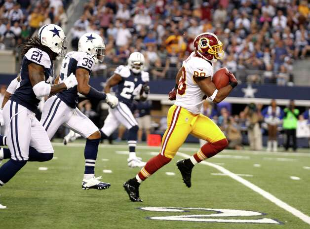 Washington Redskins wide receiver Pierre Garcon (88) out sprints Dallas Cowboys' Mike Jenkins (21), Brandon Carr (39) and Morris Claiborne (24) to the end zone for a touchdown in the first half of an NFL football game Thursday, Nov. 22, 2012 in Arlington, Texas. (AP Photo/Tim Sharp) Photo: Tim Sharp, Associated Press / FR62992 AP