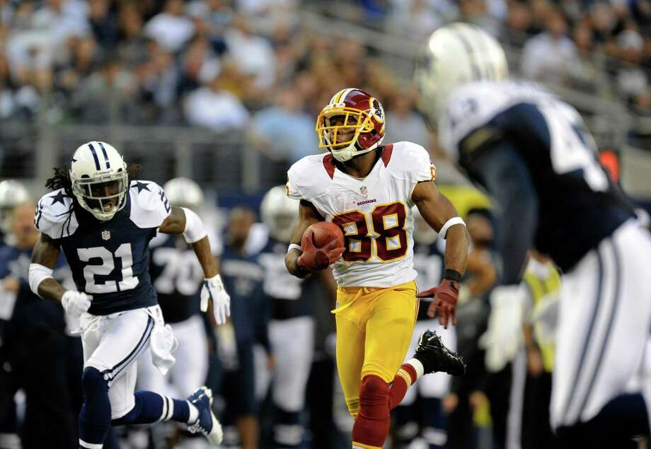 Dallas Cowboys' Mike Jenkins (21) and Gerald Sensabaugh, right, give chase as Washington Redskins wide receiver Pierre Garcon (88) sprints for the end zone and scores in the first half of an NFL football game Thursday, Nov. 22, 2012, in Arlington, Texas. (AP Photo/Matt Strasen) Photo: Matt Strasen, Associated Press / FR170476 AP