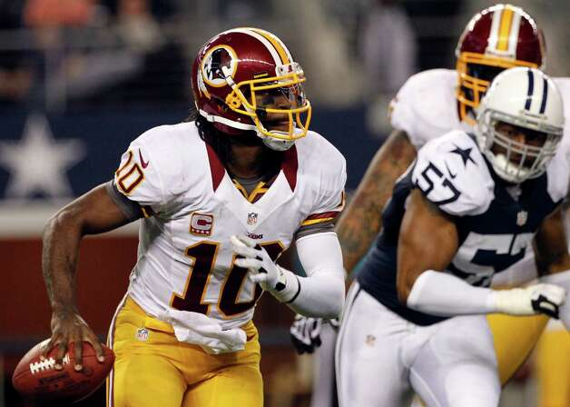 Washington Redskins quarterback Robert Griffin III (10) is chased out of the pocket by Dallas Cowboys' Victor Butler (57) in the second half of an NFL football game on Thursday, Nov. 22, 2012, in Arlington, Texas. (AP Photo/Tim Sharp) Photo: Tim Sharp, Associated Press / FR62992 AP